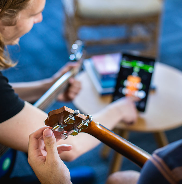 Friends tuning an Ukulele using a mobile app