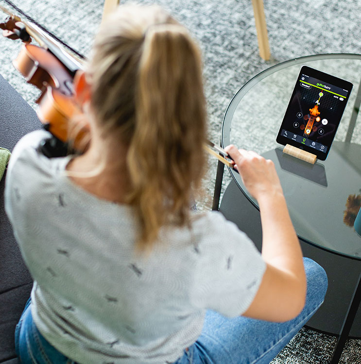 A lady tuning a violin with an mobile app